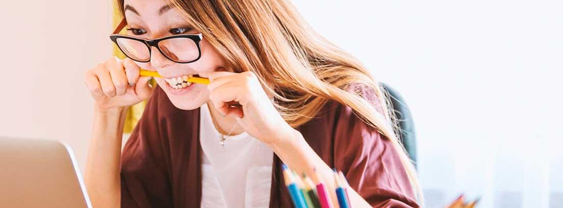 Mujer con gafas muerde lápiz amarillo mirando pantalla de ordenador portátil