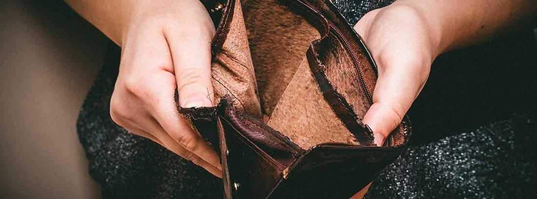 Las manos de una mujer joven muestran una billetera abierta en la que no hay dinero