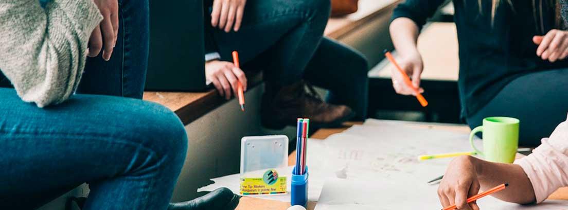 Mesa con papeles y manos con bolígrafos sobre ella rodeada de gente