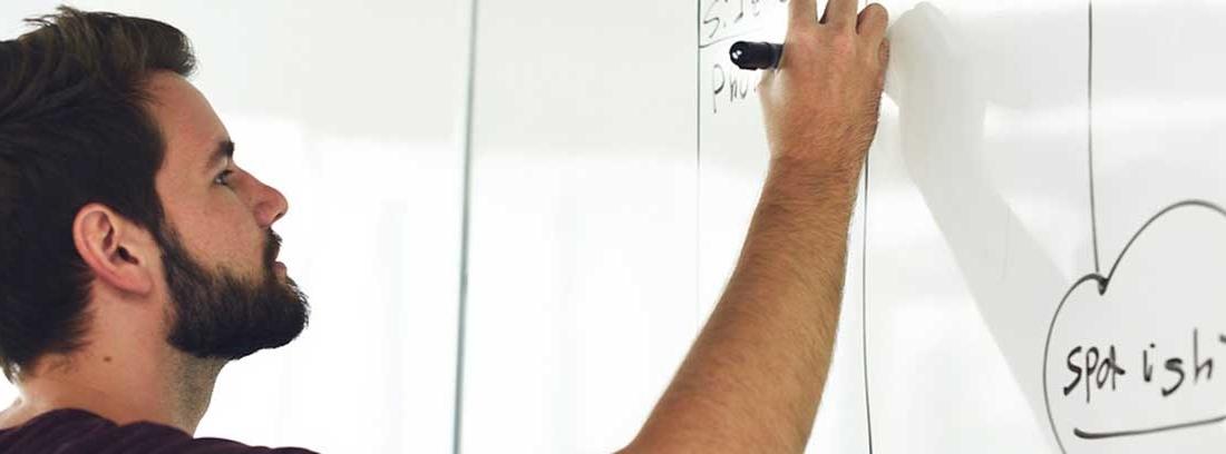 Hombre con barba sujeta rotulador sobre pared blanca con letras y organigramas