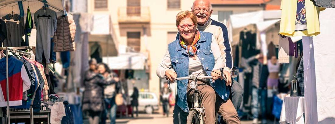 Una pareja de ancianos pasea felices en una bicicleta por un mercadillo lleno de puestos con ropa