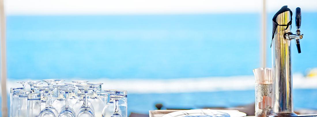 Barra con copas y vasos sobre bandeja junto a grifo con mar de fondo