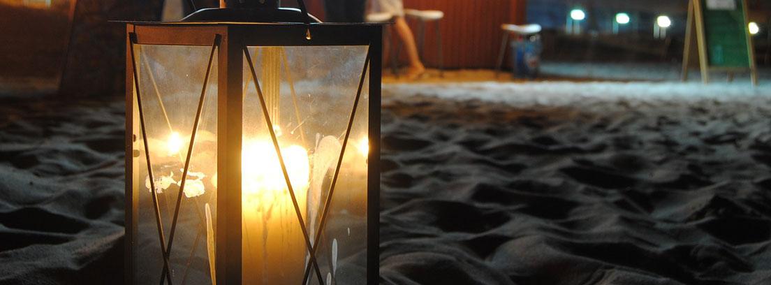 Vela dentro de farol cuadrado encendida sobre arena de playa delante de un chiringuito