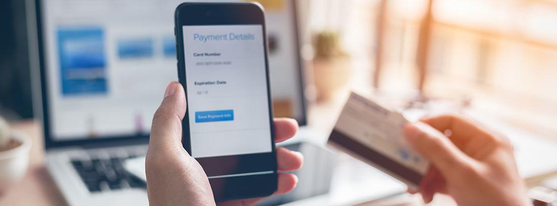 Dos manos sujetando un móvil y una tarjeta de crédito
