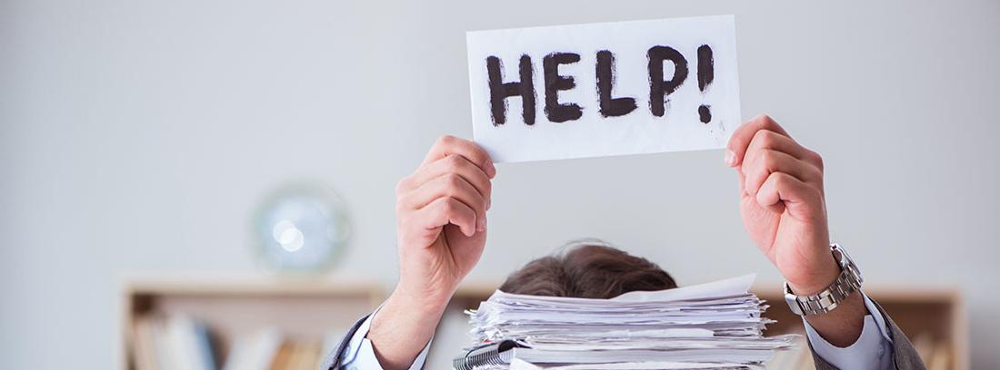 Hombre pidiendo ayuda tras montón de papeles