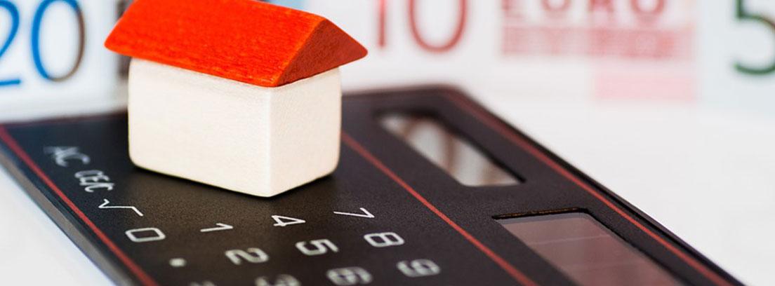 Casa de juguete y calculadora sobre fondo de dinero