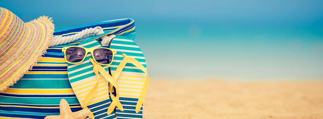 Sombrero de paja, bolso de colore amarillos y azules, chanclas a juego y gafas amarillas sobre una playa