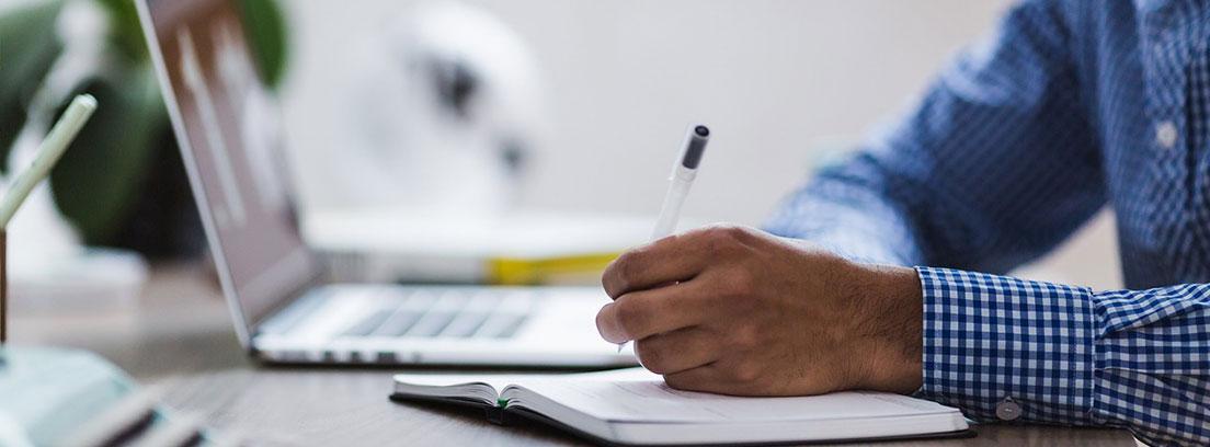 Hombre con bolígrafo sobre cuaderno y al lado de ordenador portátil