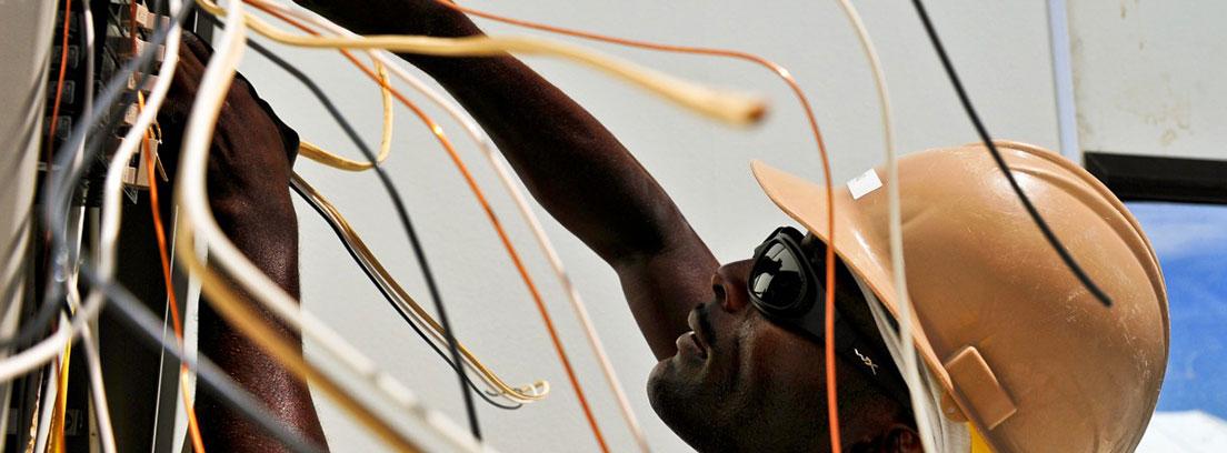 Hombre con casco y gafas de sol tocando unos cables