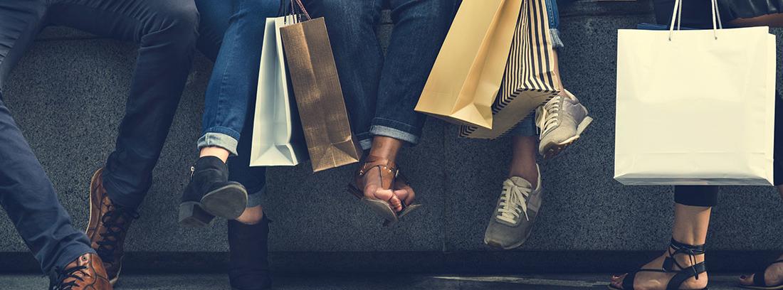 Piernas de varias personas sentadas con bolsas de la compra