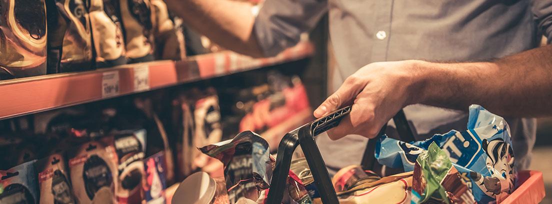 Un hombre con una cesta de supermercado en la mano comprando