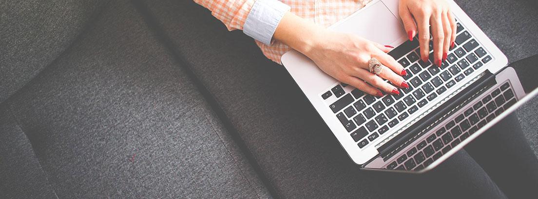 Ordenador portátil sobre las rodillas de una persona con manos sobre el teclado