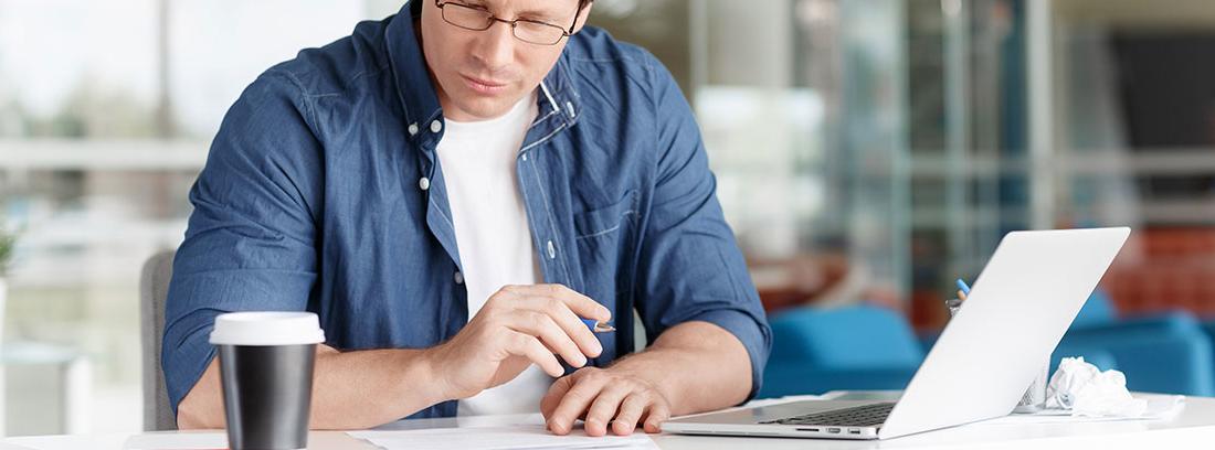Hombre con gafas sentado delante de un ordenador portátil y mira hacia papel