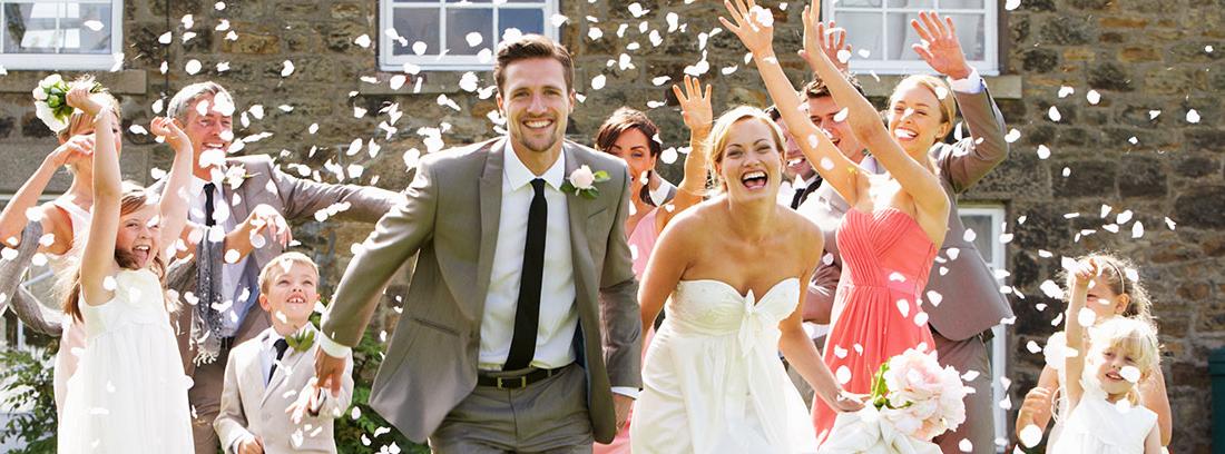 Una pareja de recién casados corre por el césped rodeada de gente