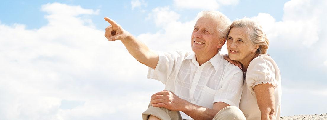 Mujer y hombre mayores sentados sobre la arena mirando a un punto lejano con gesto sonriente
