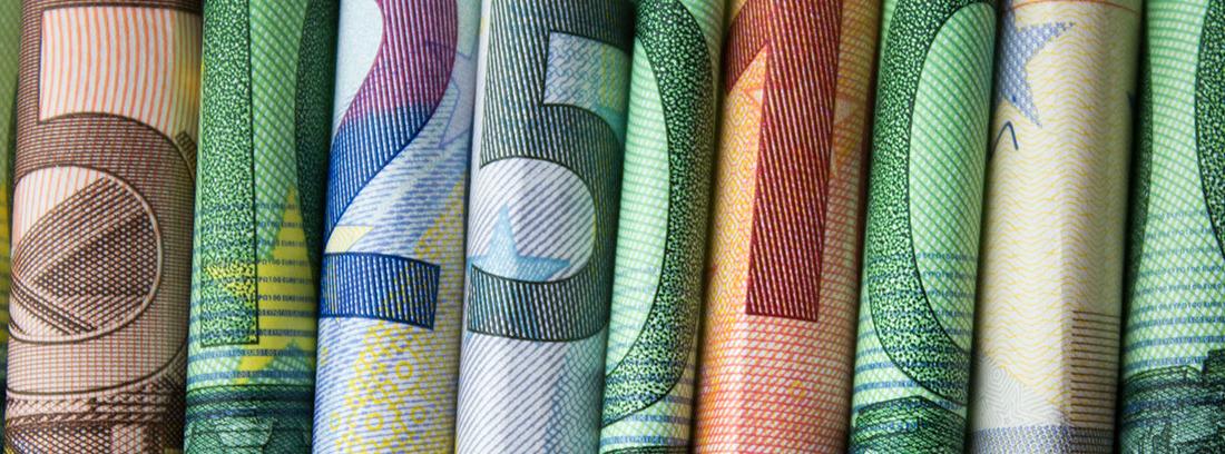 Varios billetes de distintas cantidades de Euro colocados en forma de tubo unos junto a otros