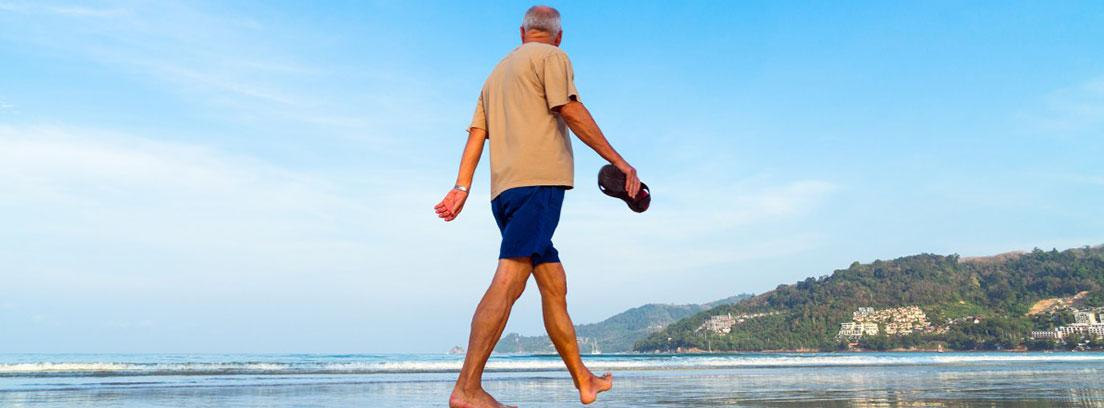 Hombre mayor descalzo caminando en la playa