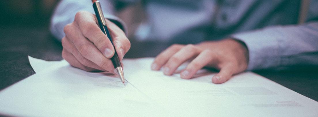 Manos con un boli escribiendo sobre unos papeles