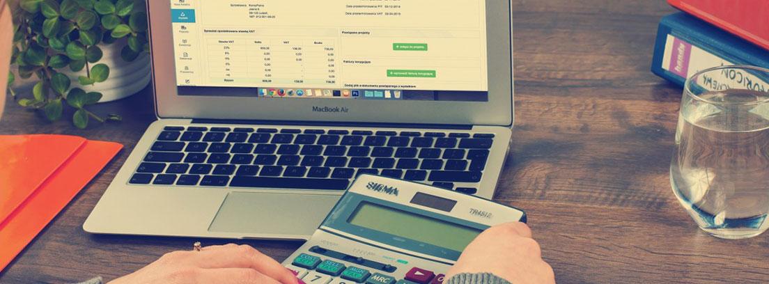 Mujer frente a una mesa con un ordenador y cogiendo una calculadora con las manos