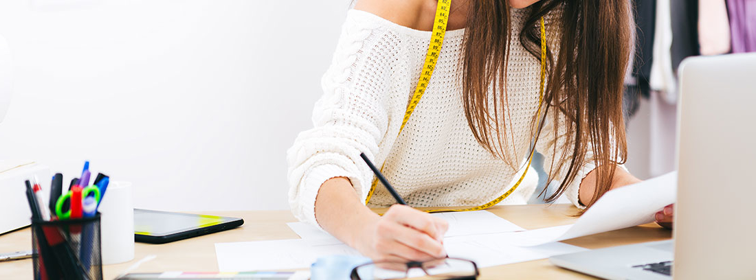 Una mujer joven con un jersey blanco y una cinta métrica al cuello de color amarillo escribe sobre un folio. En la mesa material de oficina, un ordenador y unas gafas
