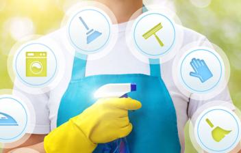 Mujer con delantal azul, guantes amarillos y un pulverizador detrás de varios símbolos de productos de limpieza