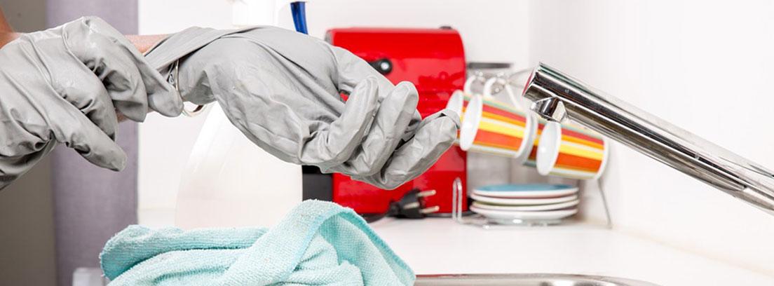 Manos con guantes grises encima de un fregadero
