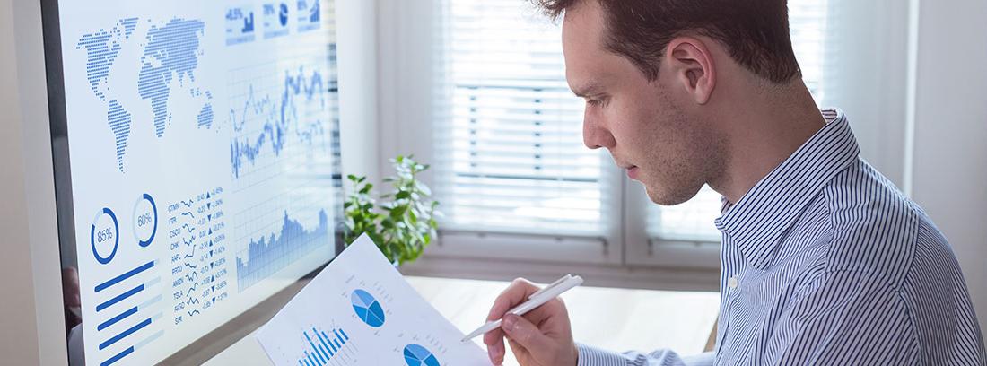 Hombre con camisa mira hoja con gráficos delante de gran monitor de ordenador