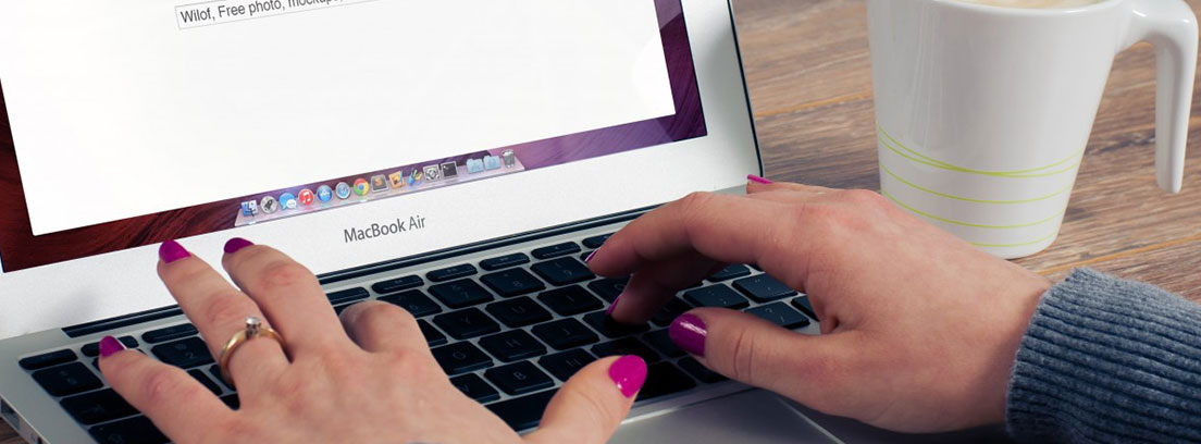 Manos sobre el teclado de un ordenador con la pantalla de inicio de Goggle y taza de café al lado