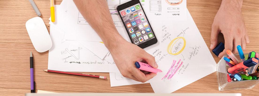 Vista cenital de una mesa de trabajo con un ordenador, un móvil y unas manos sobre unos papeles con anotaciones