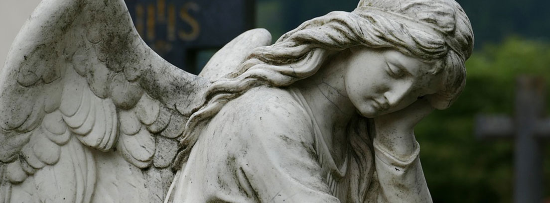 Ángel de piedra en situación reflexiva sobre una tumba en un cementerio
