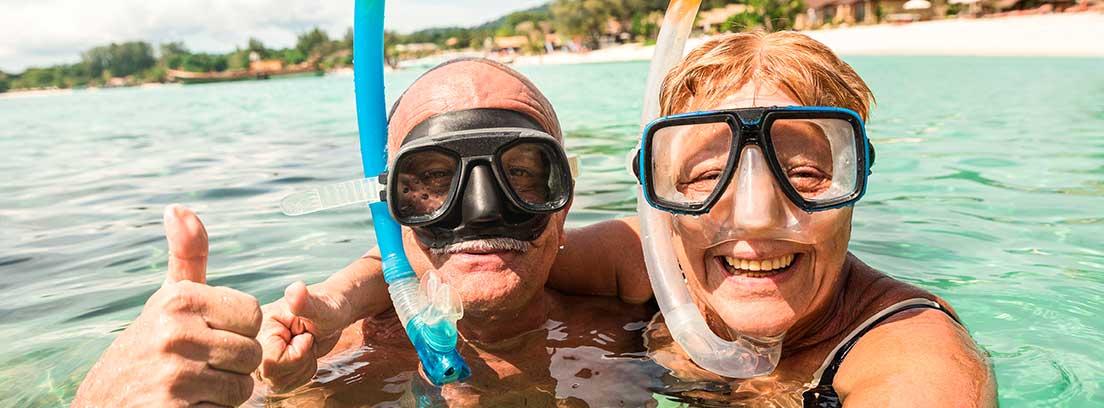Una parejas de jubilados ataviados con su equipo de snorkel se realizan un selfie dentro del agua