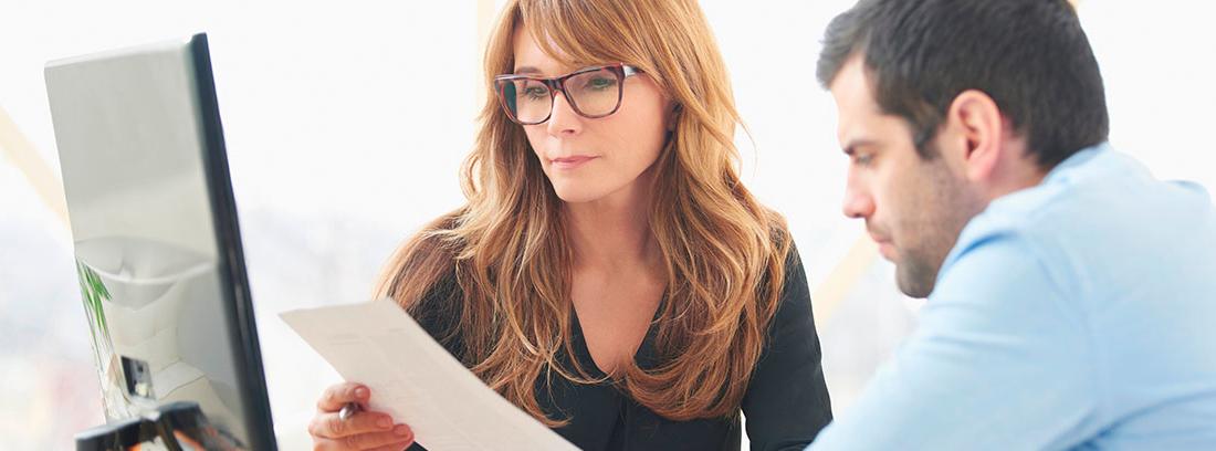Hombre y mujer leyendo unos papeles frente a una pantalla de ordenador