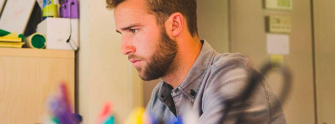 Un joven vestido con una camisa gris de manga corta sentado en una mesa de trabajo. Delante de él, difuminado un recipiente para material de oficina en el que destacan tijeras y bolígrafos