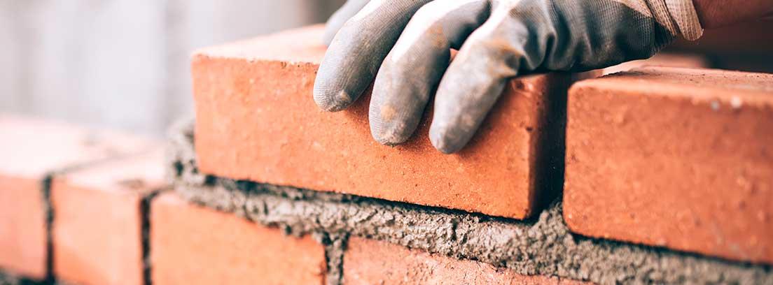 Una mano protegida por un guante gris coloca ladrillos para realizar una pared