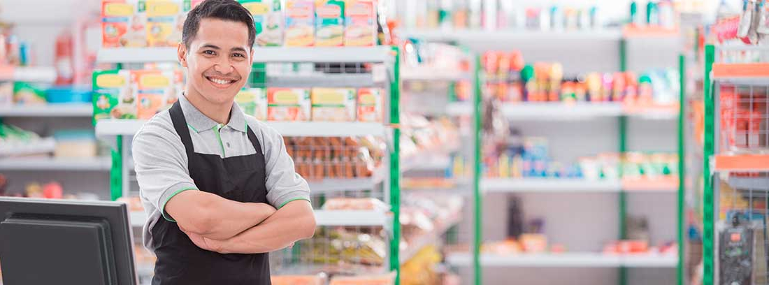 Hombre sonriente con delantal negro y brazos cruzados en el mostrador de un comercio