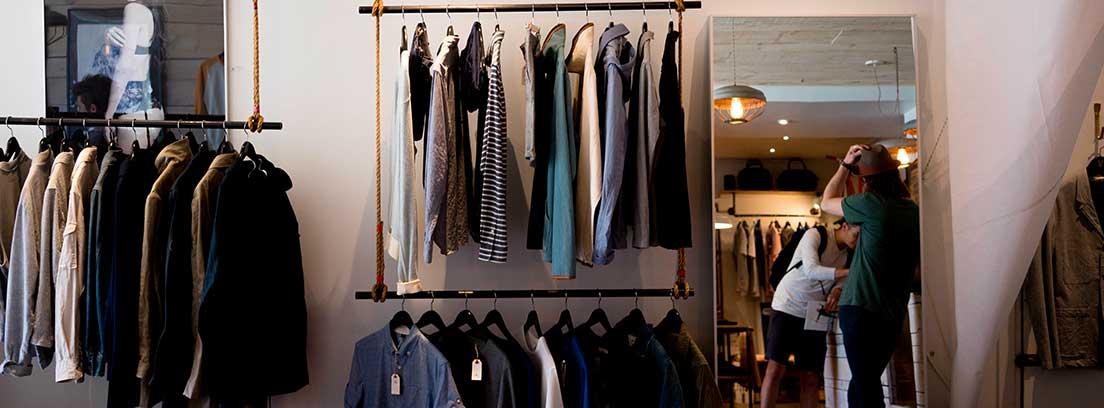 Tienda con prendas de ropa colgadas en barras