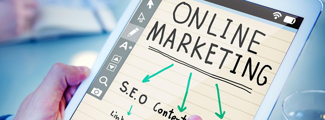 """Manos sujetando Tablet, en cuya pantalla se lee: """"Online marketing"""" para conseguir más clientes a través de Internet"""