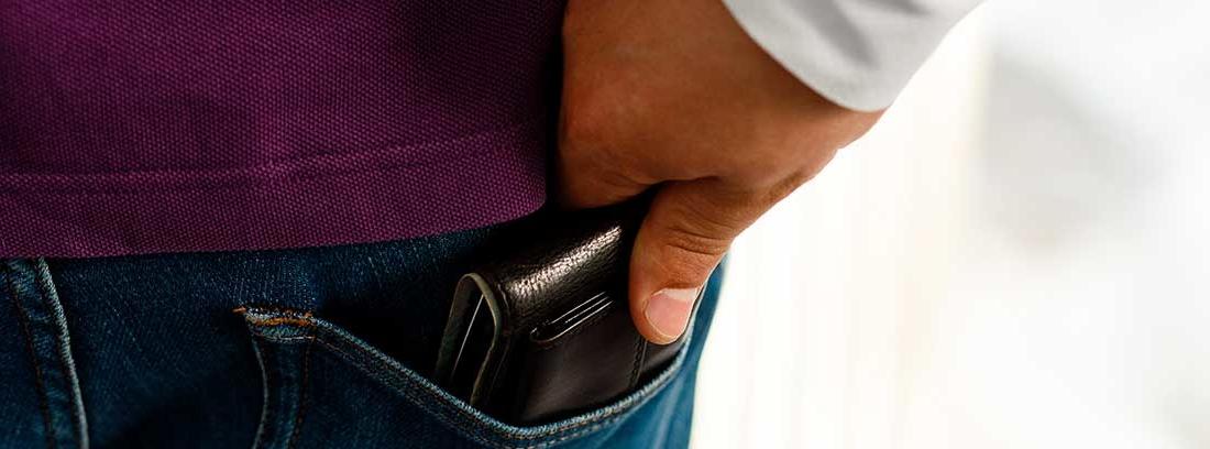 Una mano roba la cartera del bolsillo trasero de un pantalón vaquero