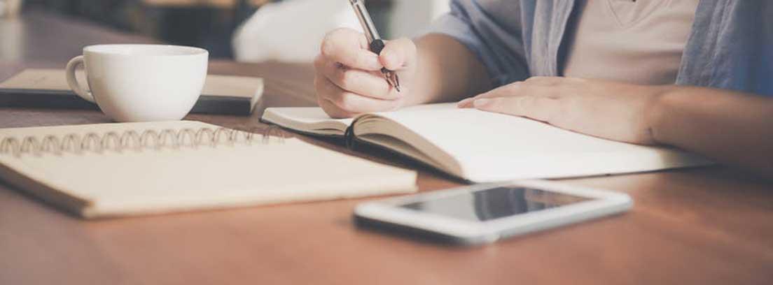 Mesa con taza blanca, cuaderno abierto, móvil y manos sobre libro abierto