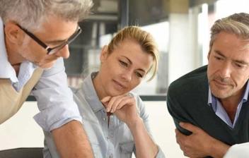 Tres personas mirando un ordenador en una oficina