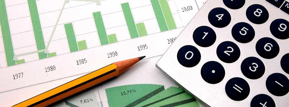Lápiz y calculadora sobre unos gráficos en verde