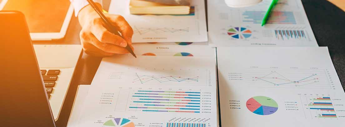 Hojas con gráficos y números sobre una mesa con mano con bolígrafo y taza blanca