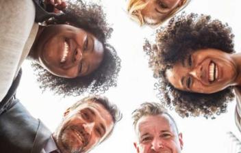 Hombres y mujeres sonrientes cogidos de los hombros entre sí formando un círculo