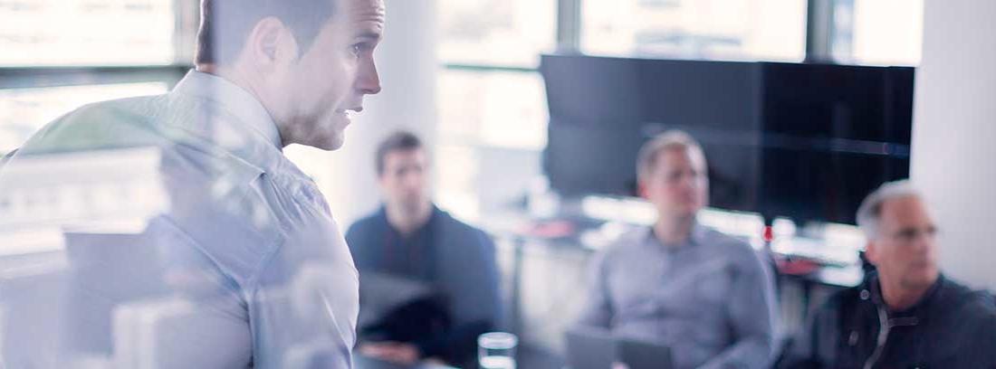 Una reunión entre varios hombres vestidos con camisa alrededor de una mesa en la que hay un proyector
