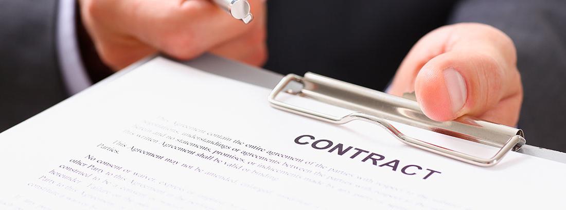 """Manos ofreciendo una carpeta con papeles en los que se puede leer """"contract"""" y un bolígrafo"""