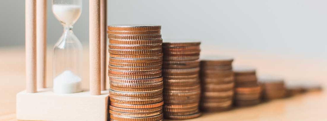 Reloj de arena junto a montones de monedas en escala