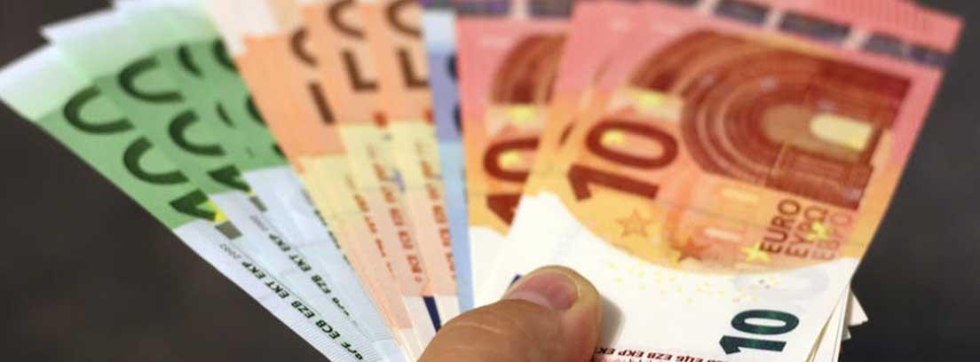 Mano sujeta billetes de euro de 100, 50 y 10 en forma de abanico