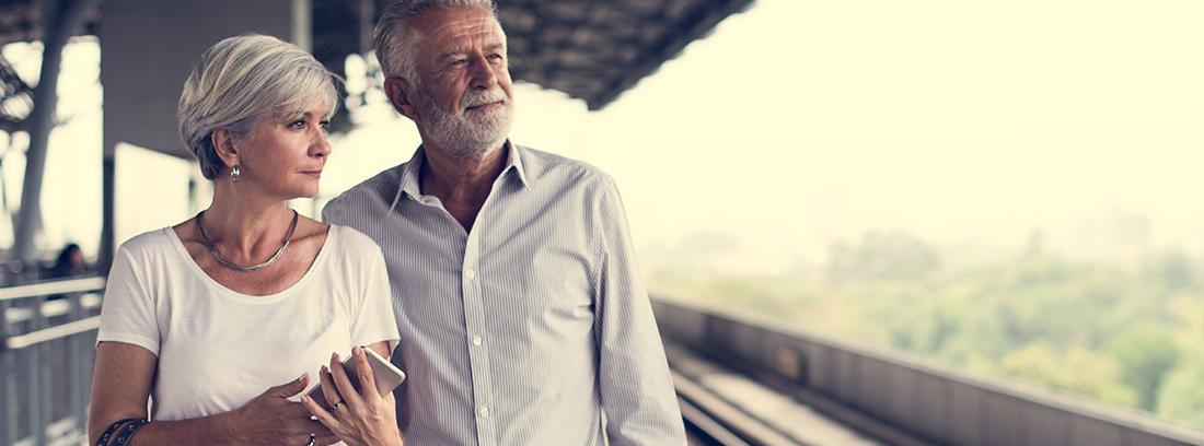 Una pareja mayor vestida con vaqueros y camisa espera en una estación de tren