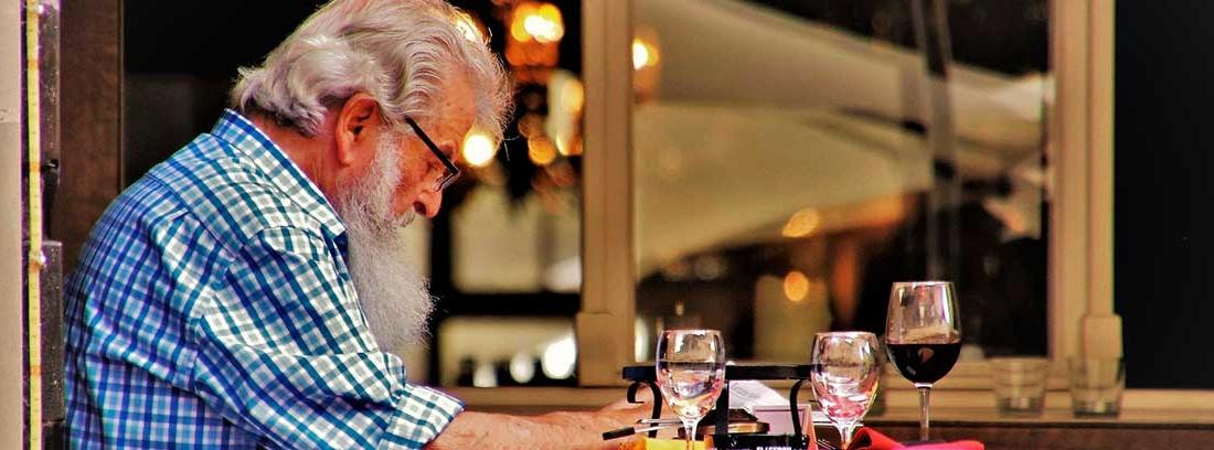Hombre mayor sentado junto a una mesa con varias copas leyendo el periódico