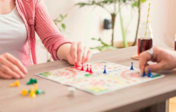 Una pareja joven juega a un juego de mesa con figuras de colores